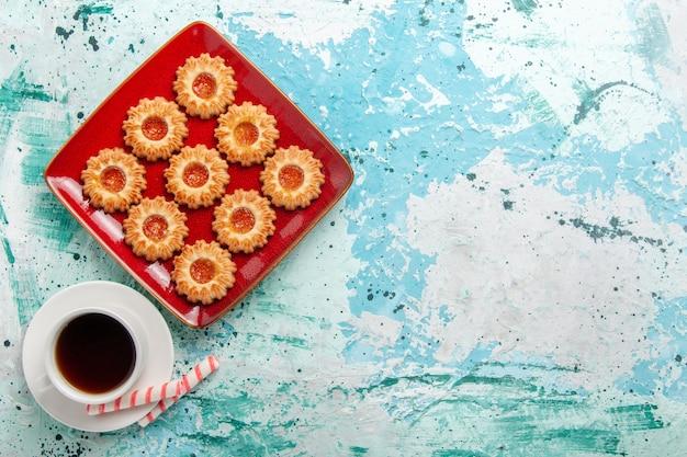 Vista superior de biscoitos doces com geleia de laranja e uma xícara de chá no fundo azul