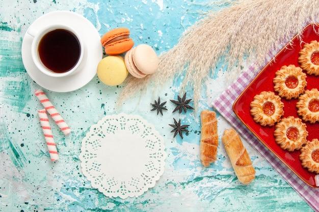 Vista superior de biscoitos doces com rosquinhas de geleia de laranja e uma xícara de chá no fundo azul
