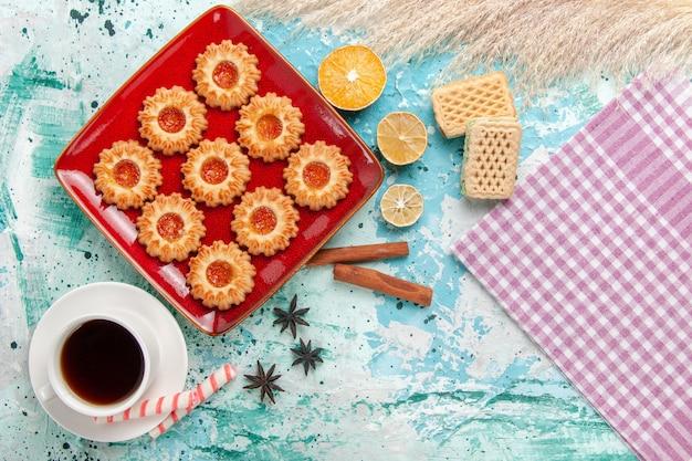 Vista superior de biscoitos doces com waffles de geleia de laranja e uma xícara de chá no fundo azul
