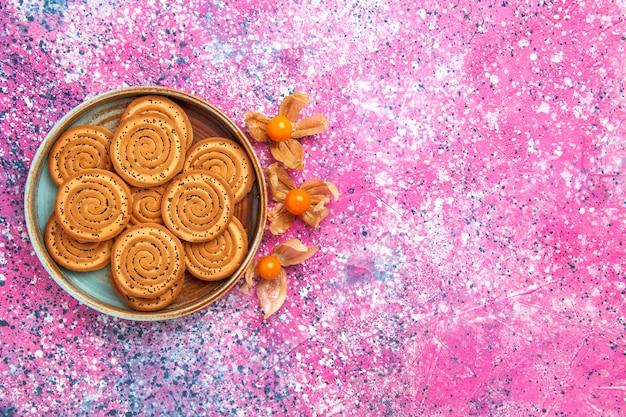 Vista superior de biscoitos doces dentro do prato na superfície rosa