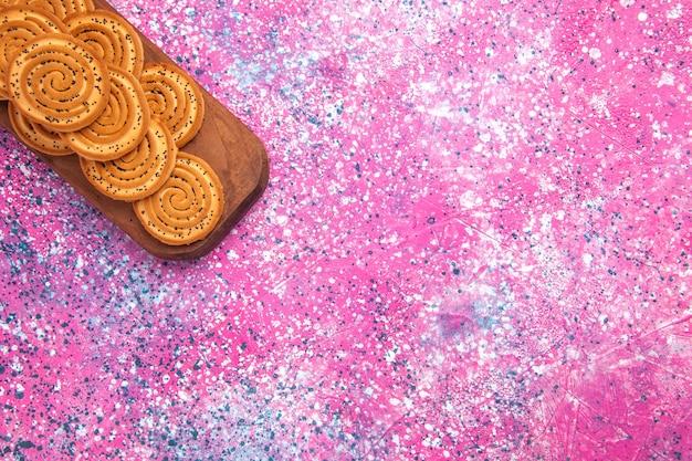 Vista superior de biscoitos doces redondos alinhados na superfície rosa