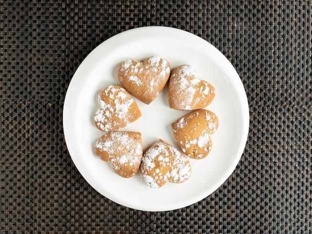 Vista superior de biscoitos em forma de coração, cobertos com açúcar em pó