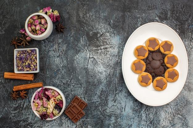 Vista superior de biscoitos em um prato branco e tigelas de flores secas e chocolates em solo cinza
