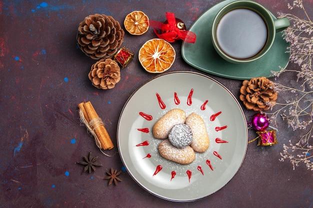 Vista superior de biscoitos saborosos com uma xícara de chá no preto