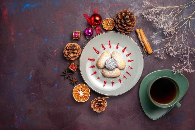 Vista superior de biscoitos saborosos, doces de açúcar em pó com uma xícara de chá no preto