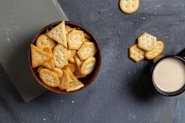 Vista superior de biscoitos saborosos salgados com copo de leite no fundo cinza.