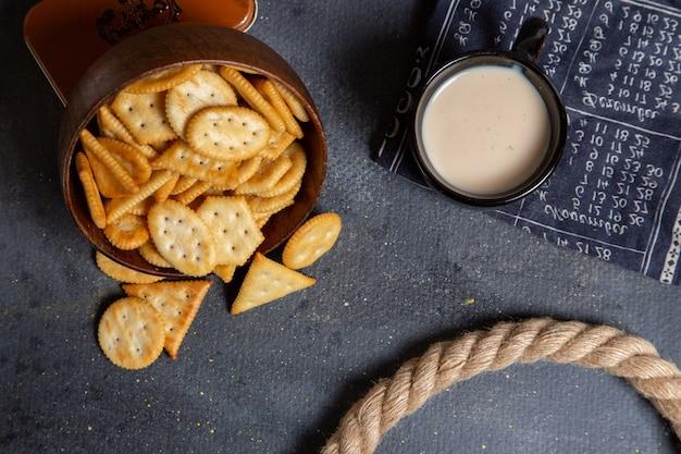 Vista superior de biscoitos salgados diferentes com um copo de leite no fundo cinza.