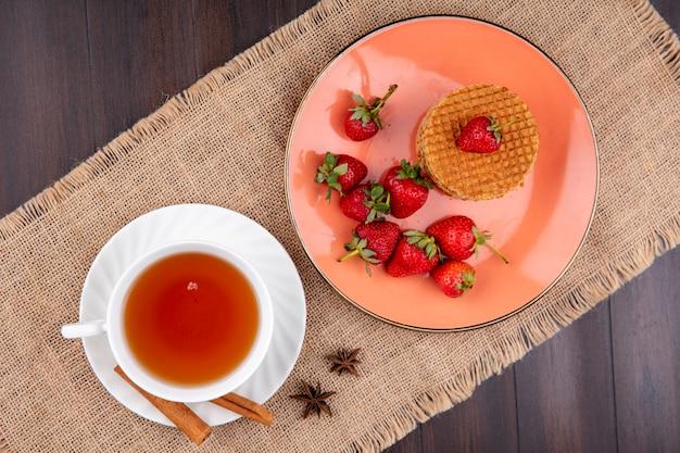 Vista superior de biscoitos waffle e morangos no prato e xícara de chá com canela no pires de saco e superfície de madeira