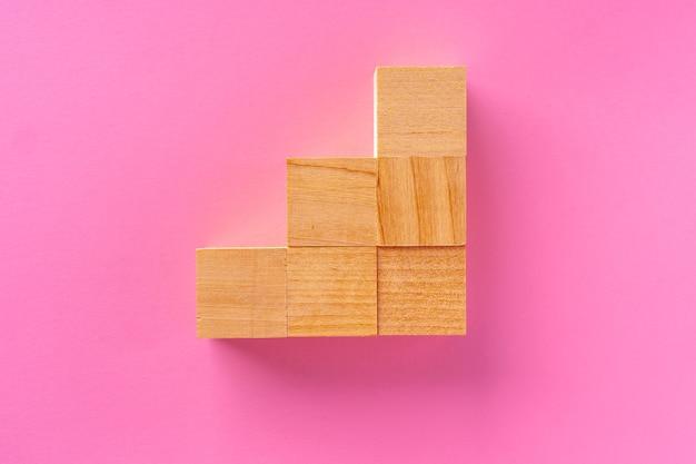 Vista superior de blocos de madeira de brinquedo em fundo rosa