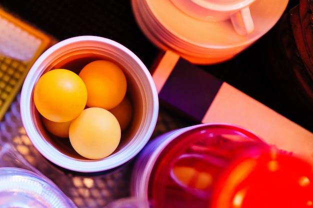 Vista superior de bolas alaranjadas do pong do sibilo dentro do vidro de cerveja vermelho para jogar o pong da cerveja.