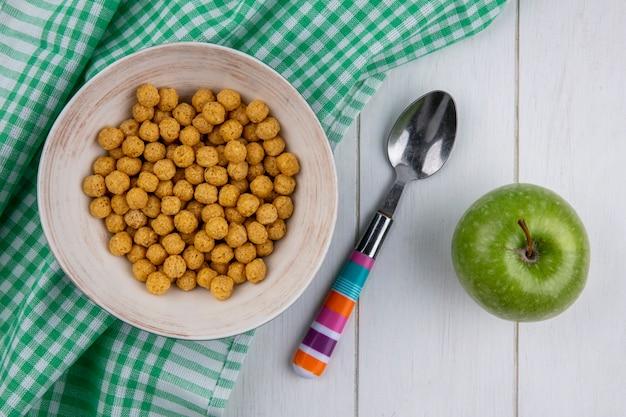 Vista superior de bolas de milho em uma toalha xadrez com uma colher colorida e uma maçã verde em uma superfície branca