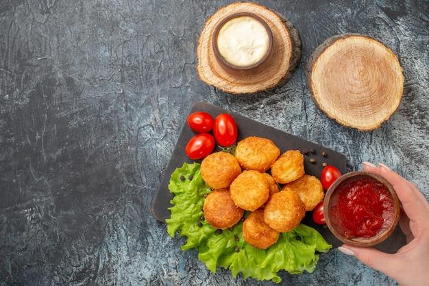 Vista superior de bolas de queijo frito em tigelas de molho de tábua de corte na tábua de madeira