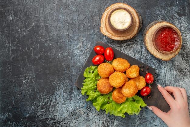 Vista superior de bolas de queijo frito em uma tábua de cortar em tigelas de molho de mão feminina em tábuas de madeira