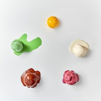 Vista superior de bolas multicoloridas de sorvete derretido - branco, marrom, verde, amarelo, vermelho sobre um fundo branco. conceito de alimentos frescos de verão.