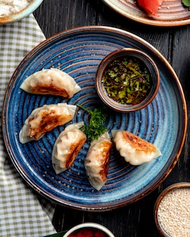 Vista superior de bolinhos asiáticos tradicionais com carne e legumes, servidos com molho de soja em um prato na mesa rústica
