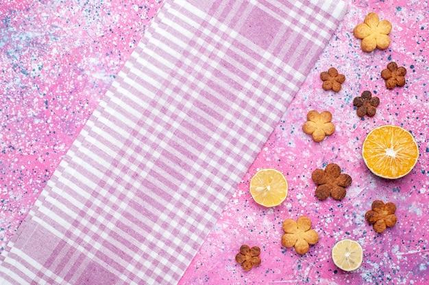 Vista superior de bolinhos com rodelas de limão na superfície rosa