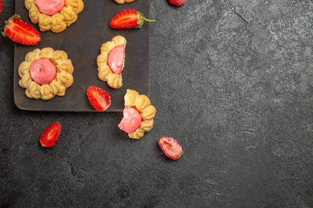 Vista superior de bolinhos de açúcar com creme de morango na superfície cinza