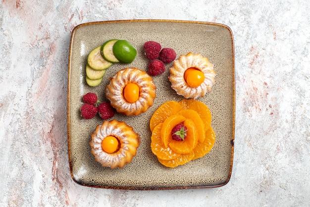 Vista superior de bolinhos deliciosos com frutas fatiadas em branco