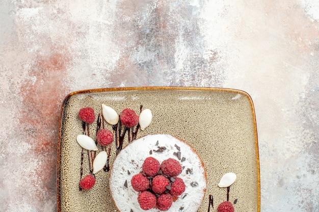 Vista superior de bolo acabado de fazer com framboesas para bebês em uma bandeja branca na mesa de cores misturadas