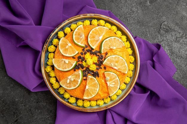 Vista superior de bolo com prato de limão de um bolo apetitoso com fatias de frutas cítricas na toalha de mesa roxa