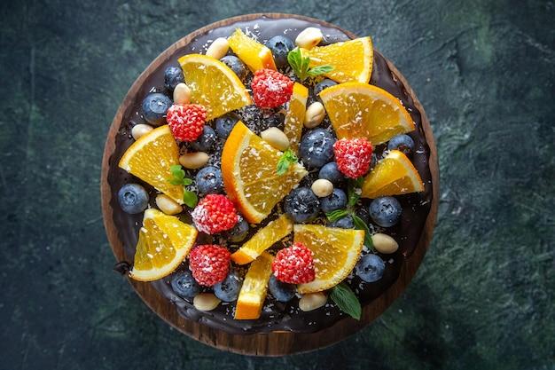 Vista superior de bolo de chocolate gostoso com frutas frescas no escuro