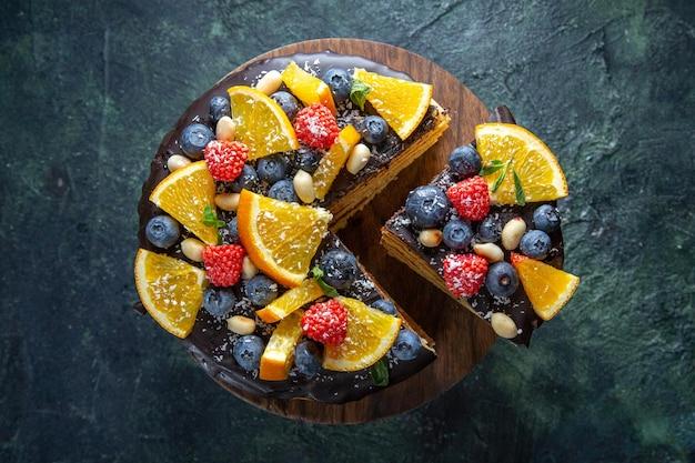 Vista superior de bolo de chocolate gostoso com frutas no escuro