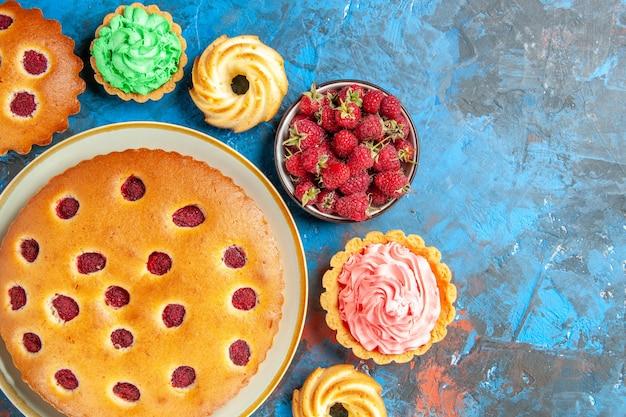 Vista superior de bolo de framboesa em prato oval cercado por biscoitos, tortinhas pequenas e tigela com frutas na superfície azul
