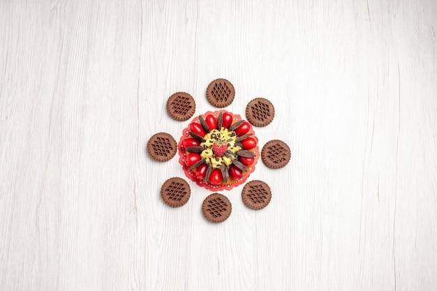 Vista superior de bolo de frutas vermelhas sobre o guardanapo de renda oval vermelha arredondado com biscoitos na mesa de madeira branca
