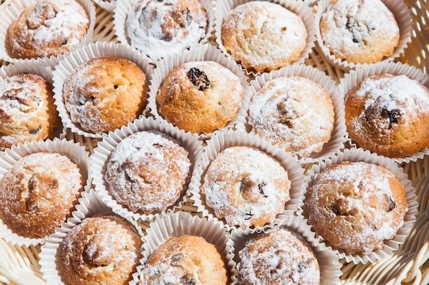 Vista superior de bolos cozidos frescos em copos de papel. conjunto de cupcakes polvilhados com açúcar de confeiteiro.