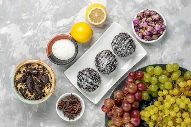 Vista superior de bolos de chocolate com limão e uvas na superfície branca