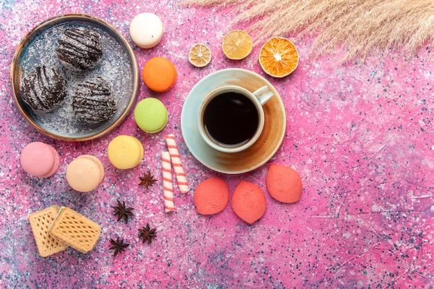 Vista superior de bolos de chocolate com macarons franceses em rosa claro