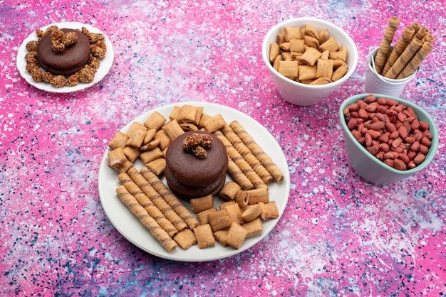 Vista superior de bolos de chocolate com nozes e biscoitos no fundo colorido.