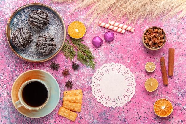 Vista superior de bolos de chocolate com uma xícara de chá em rosa claro