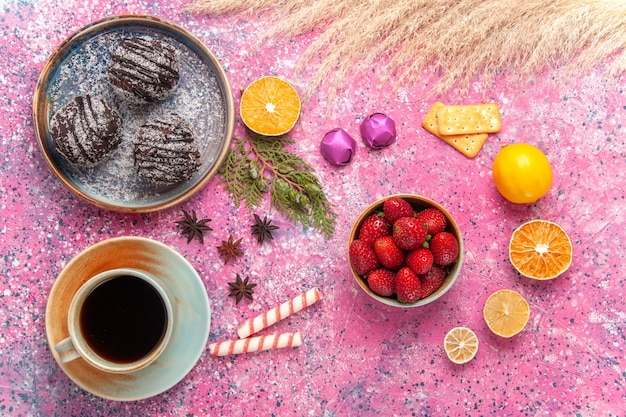 Vista superior de bolos de chocolate com uma xícara de chá rosa