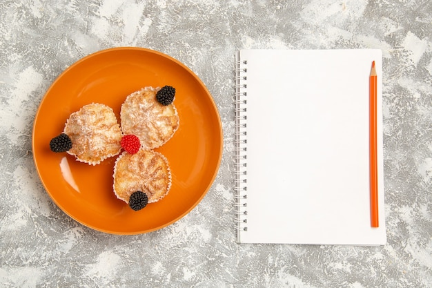 Vista superior de bolos de massa saborosa com açúcar em pó e bloco de notas no fundo branco