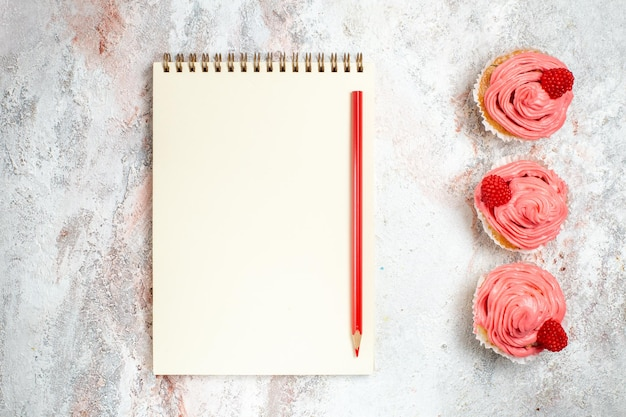 Vista superior de bolos de morango rosa com creme e bloco de notas na superfície branca
