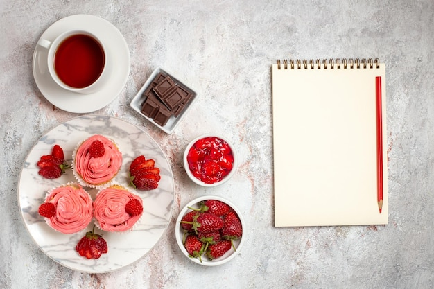 Vista superior de bolos de morango rosa com creme e xícara de chá na superfície branca