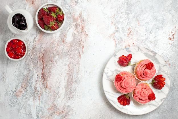 Vista superior de bolos de morango rosa com geleia e barras de chocolate na superfície branca