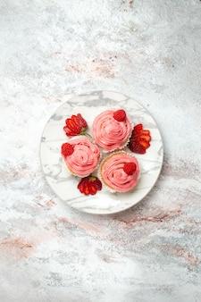Vista superior de bolos de morango rosa com morangos vermelhos frescos na superfície branca