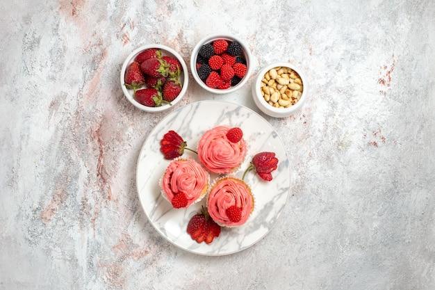 Vista superior de bolos de morango rosa com nozes na superfície branca