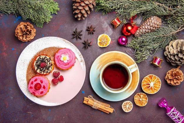 Vista superior de bolos deliciosos doces com frutas e xícara de chá no preto