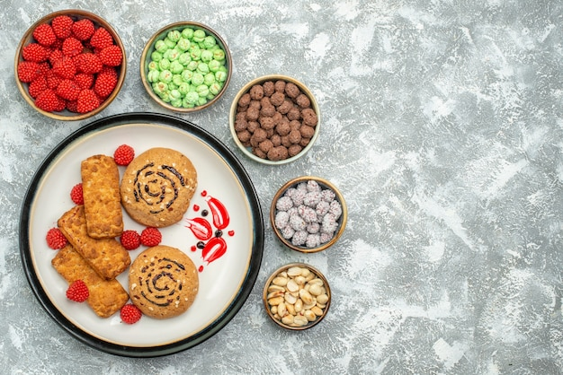 Vista superior de bolos doces com doces no fundo branco bolo de biscoito doce biscoito
