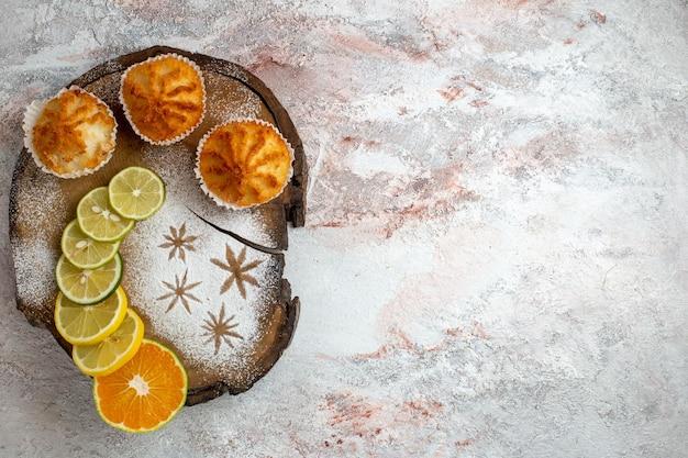 Vista superior de bolos doces com rodelas de limão em uma superfície branca clara