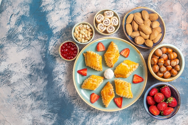Vista superior de bolos doces deliciosos com frutas e nozes na mesa azul