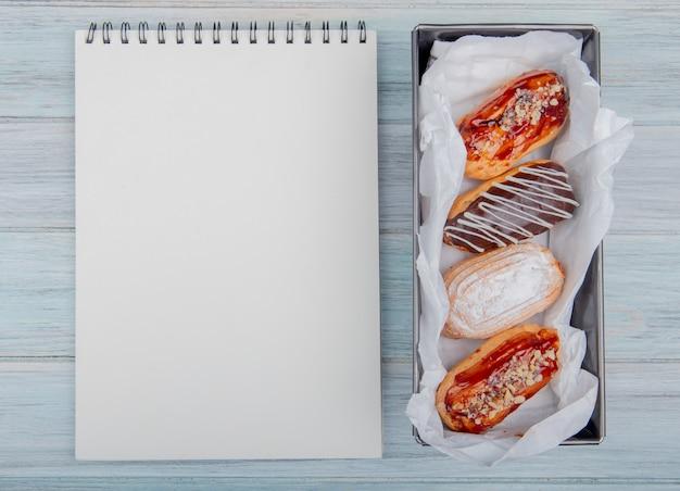 Vista superior de bolos e bloco de notas em fundo de madeira com espaço de cópia