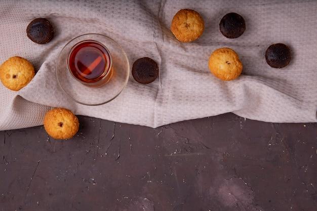 Vista superior de bolos e chá preto em vidro armudu na toalha da mesa