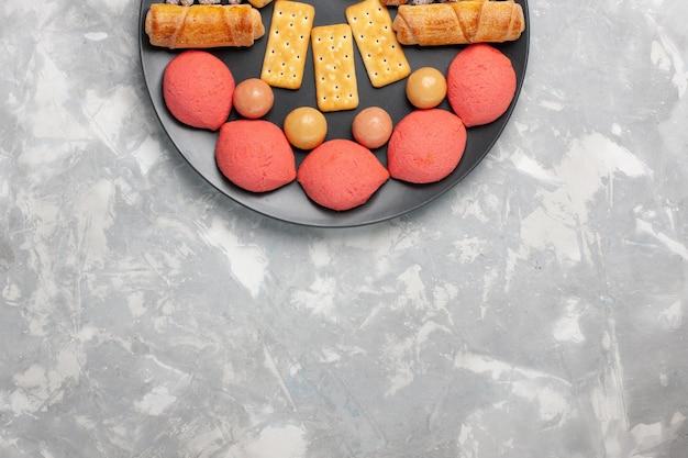 Vista superior de bolos saborosos com bagels e doces na superfície branca clara