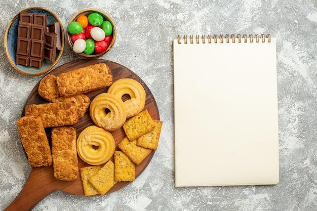 Vista superior de bolos saborosos com biscoitos e doces no fundo branco