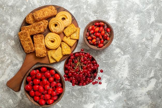 Vista superior de bolos saborosos com biscoitos e frutas no fundo branco