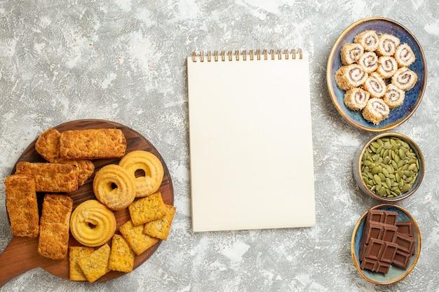 Vista superior de bolos saborosos com doces e biscoitos em fundo branco claro